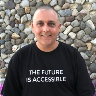 "Picture of Mike Marotta in front of rock wall wearing a shirt that says ""The Future is Accessible"""